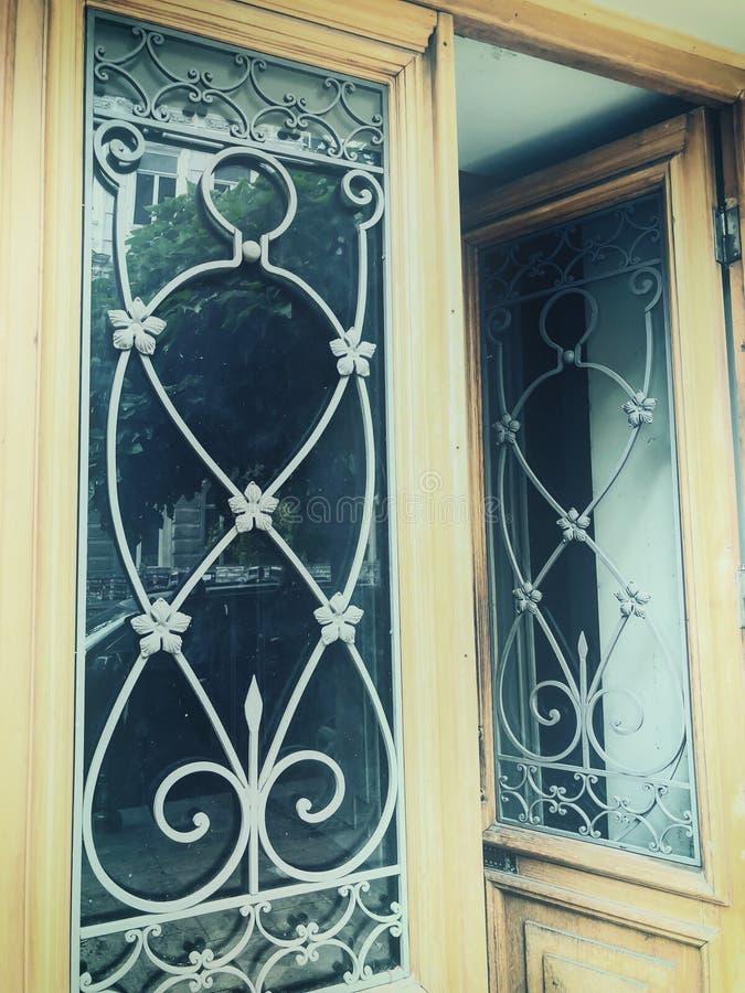 一个大厦的反射在街道上的在与铁装饰装饰品的玻璃木门 老第比利斯建筑学 库存图片