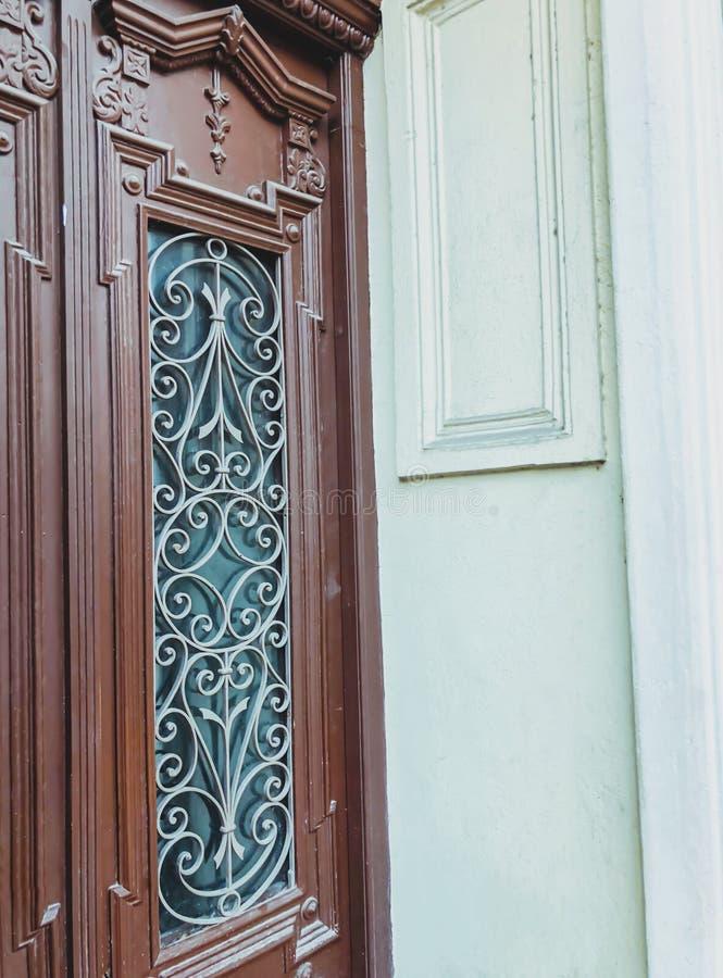 一个大厦的玻璃木门在街道上的有铁装饰装饰品的 老第比利斯建筑学 免版税库存照片