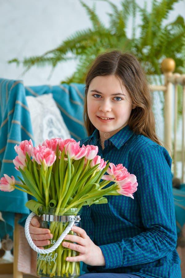 一个女孩的春天画象有桃红色郁金香的 库存图片