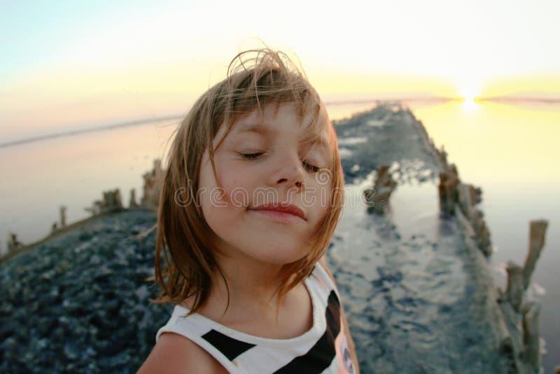 一个女孩特写镜头的夏天画象,在日落,女孩的一个盐湖有满足和嬉戏的面孔的 免版税图库摄影