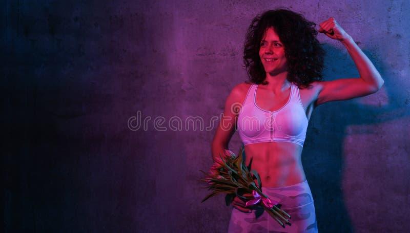 一个女运动员的画象一个田径服身分的在拿着郁金香的花束一个混凝土墙,被隔绝在霓虹灯 免版税库存图片