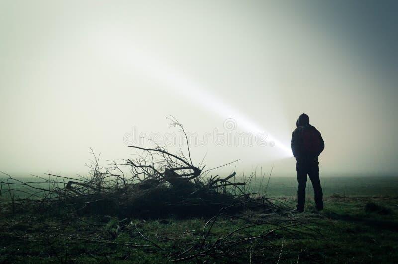 一个孤立戴头巾图的一个令人毛骨悚然的剪影在领域的在与火炬的有雾的夜 以黑暗编辑 免版税库存照片