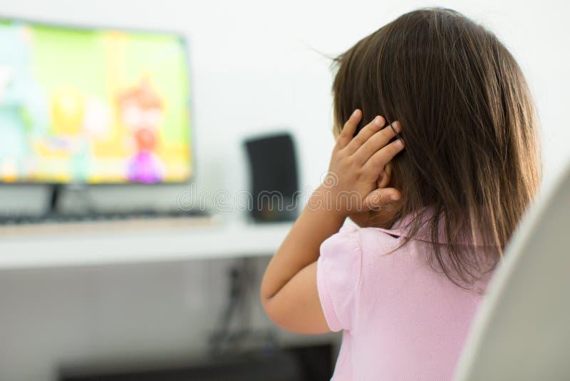 一个害怕的孩子,害怕从电视的大声的声音 孤独性 免版税库存图片