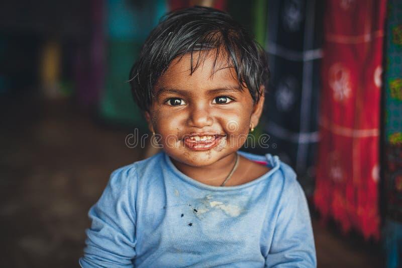 一个小印度女孩看照相机和微笑摄影师 巧克力婴孩 老衣裳的印度孩子 画象  免版税库存图片