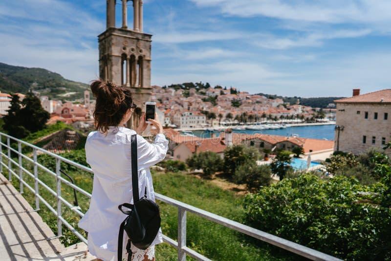 一个小克罗地亚镇的背景的年轻美女 免版税图库摄影
