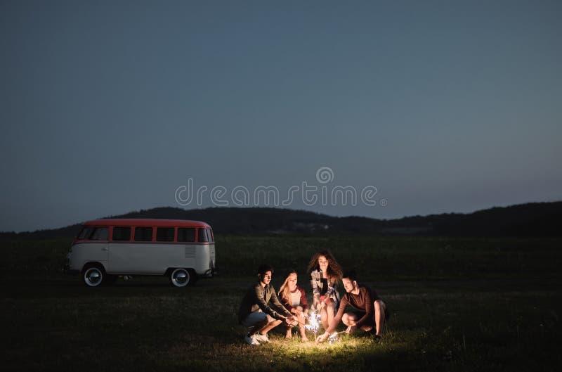 一个小组有站立户外在黄昏的闪烁发光物的朋友 库存照片