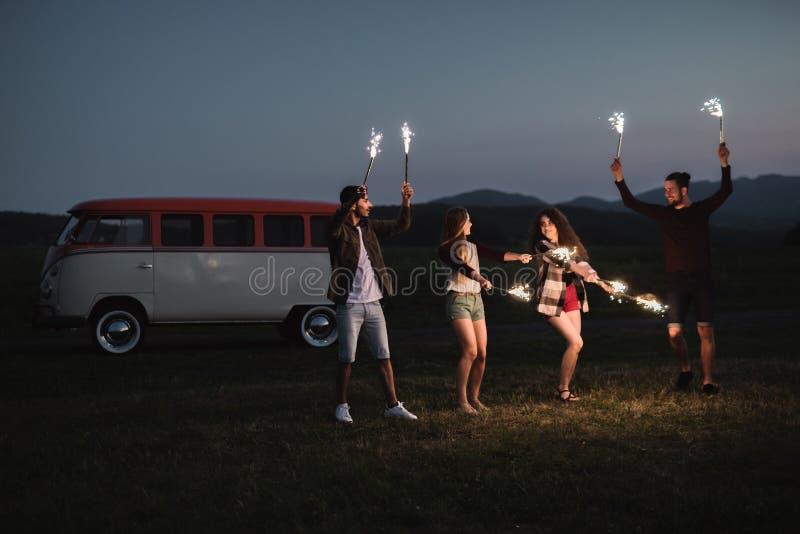 一个小组有站立户外在黄昏的闪烁发光物的朋友 免版税图库摄影
