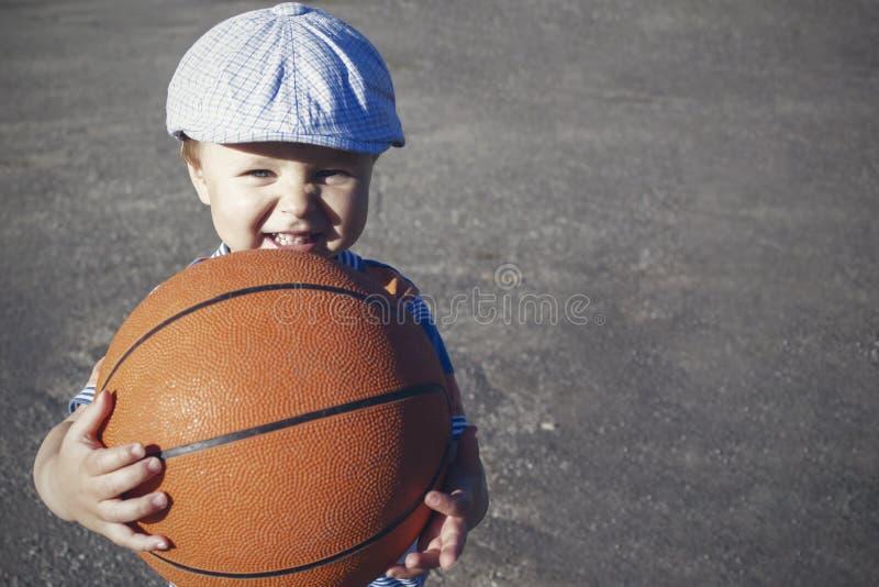 一个小男孩举行篮球,街道篮球操场 免版税图库摄影