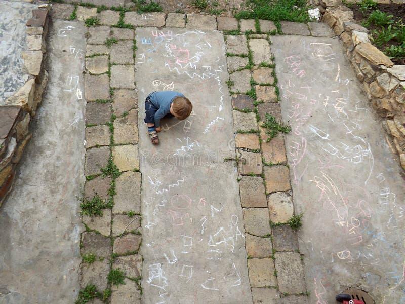 一个小男孩在与白垩的混凝土画 免版税图库摄影