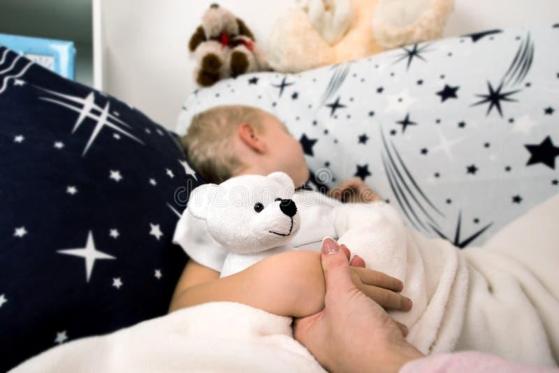 一个小男孩在床上在 妈妈以前轻轻地亲吻它睡觉 免版税库存照片