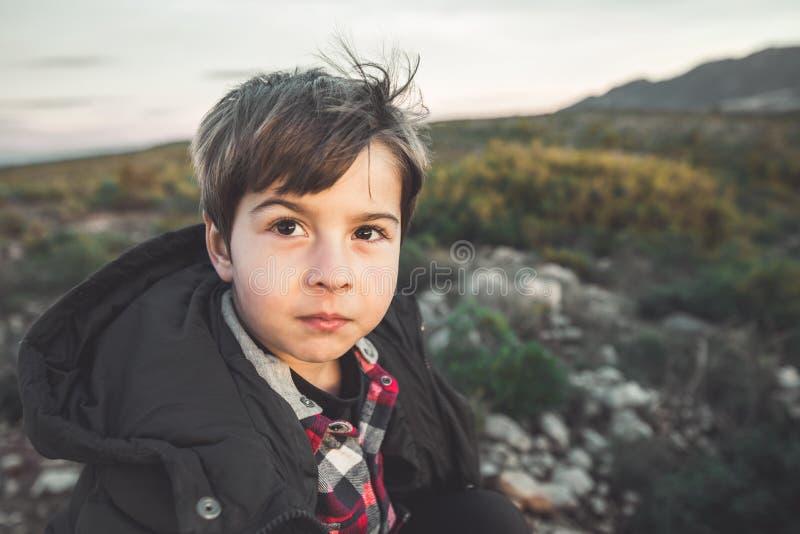 一个小男孩和微笑的画象有滑稽的表示的在乡下 愉快的子项 免版税图库摄影