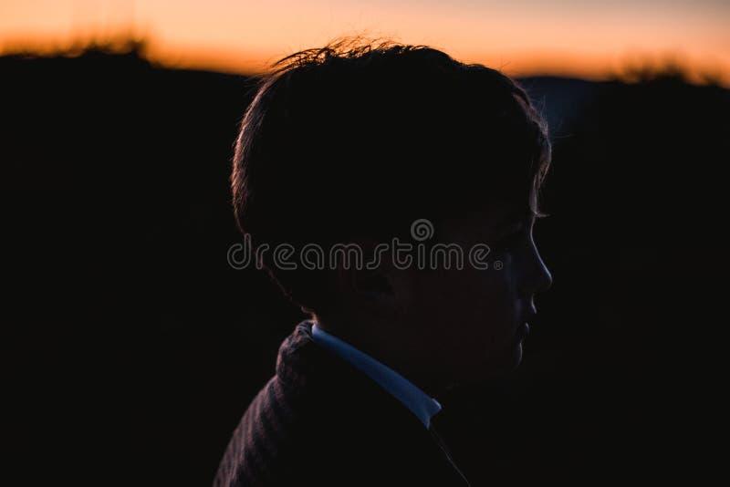 一个小男孩的剪影的画象日落的在乡下 孩子本质上 库存照片