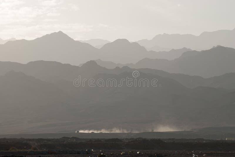 一个山土坎的剪影的风景在阴霾的在一个距离和一条多灰尘的尾巴在游遍的汽车后 免版税库存照片