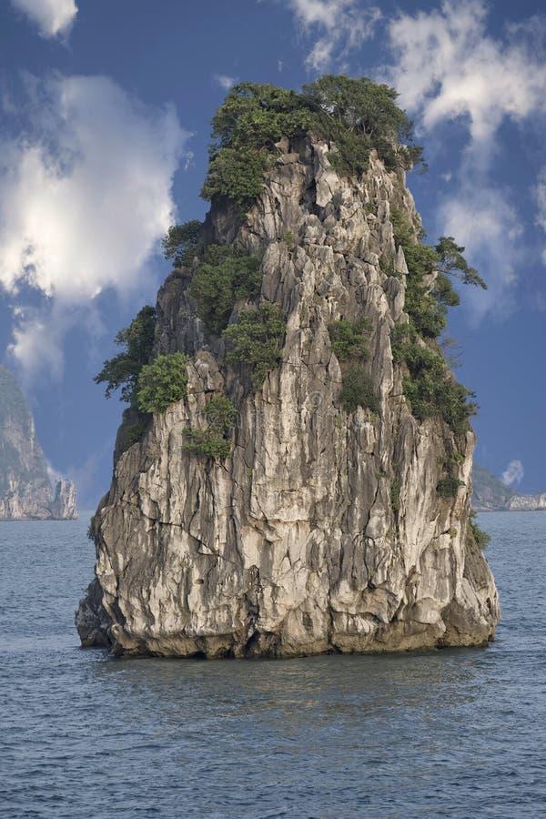 一个岩石在有天空蔚蓝和白色云彩的海 图库摄影