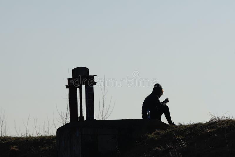 一个年轻常设女孩的剪影跑步的运动服的在金属建筑附近 放松在浪漫大气本质上 的treadled 库存照片