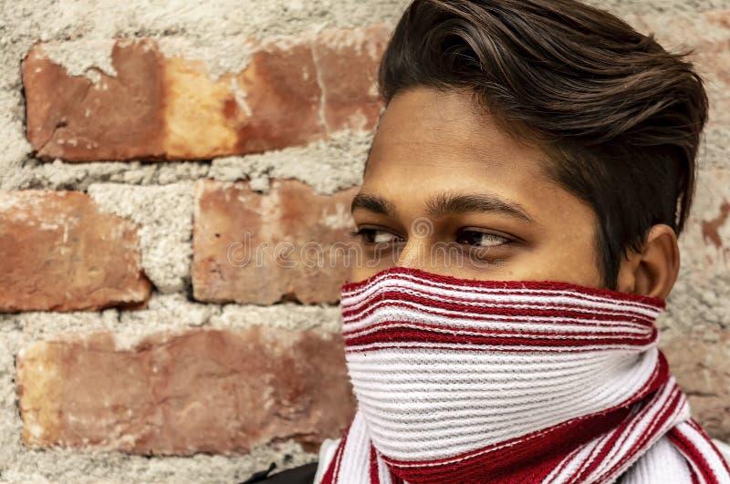 一个年轻男性模型的侧视图画象与围巾被盖的面孔的 图库摄影