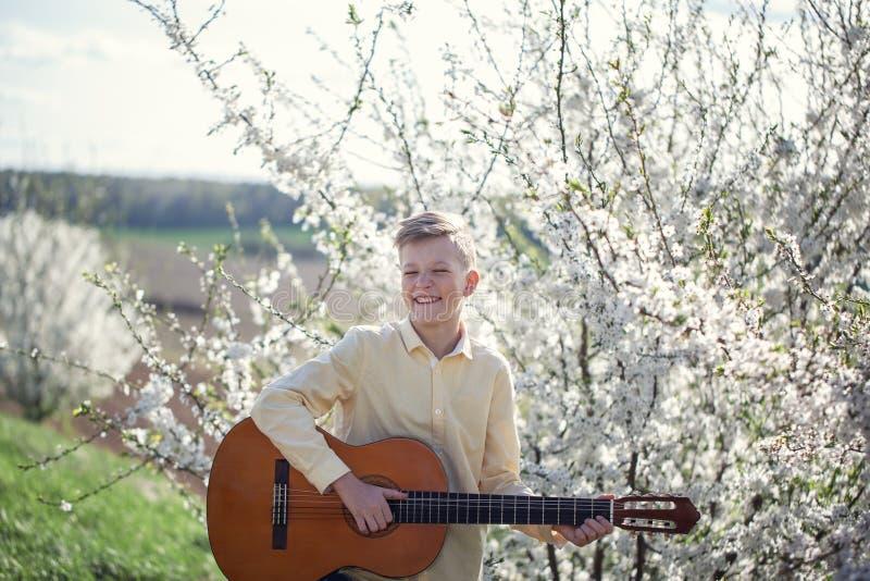 一个年轻11岁的男孩身分的画象在春天公园和使用吉他 免版税库存图片