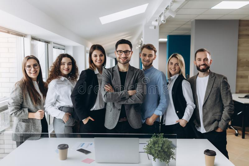 一个微笑的小组的画象连续站立一起在一个明亮的现代办公室的不同的公司同事 免版税库存图片