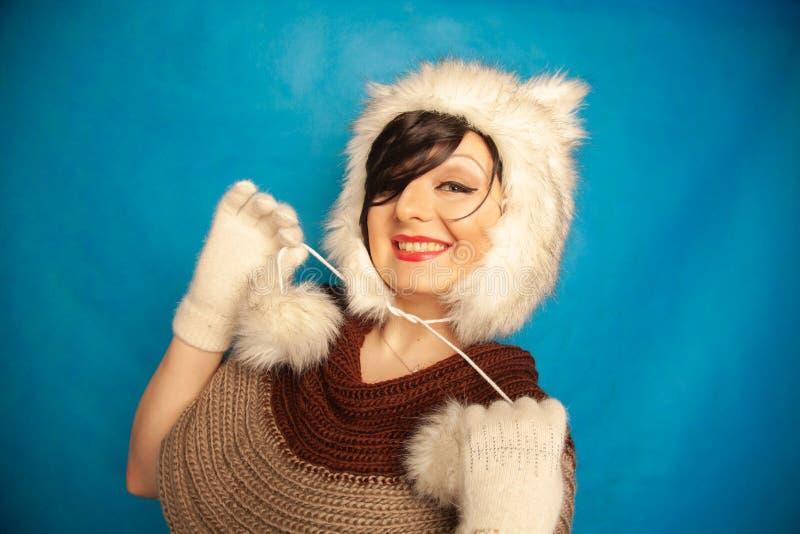 一个毛皮白色冬天帽子的迷人的白种人女孩有猫耳朵的微笑并且享有在蓝色坚实背景的生活在演播室Al 免版税库存图片