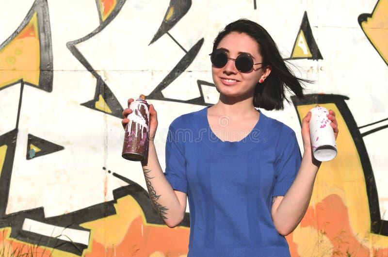 一个情感女孩的画象有黑发和穿甲的 一个女孩的照片有湿剂油漆罐头的在街道画的手上 库存图片