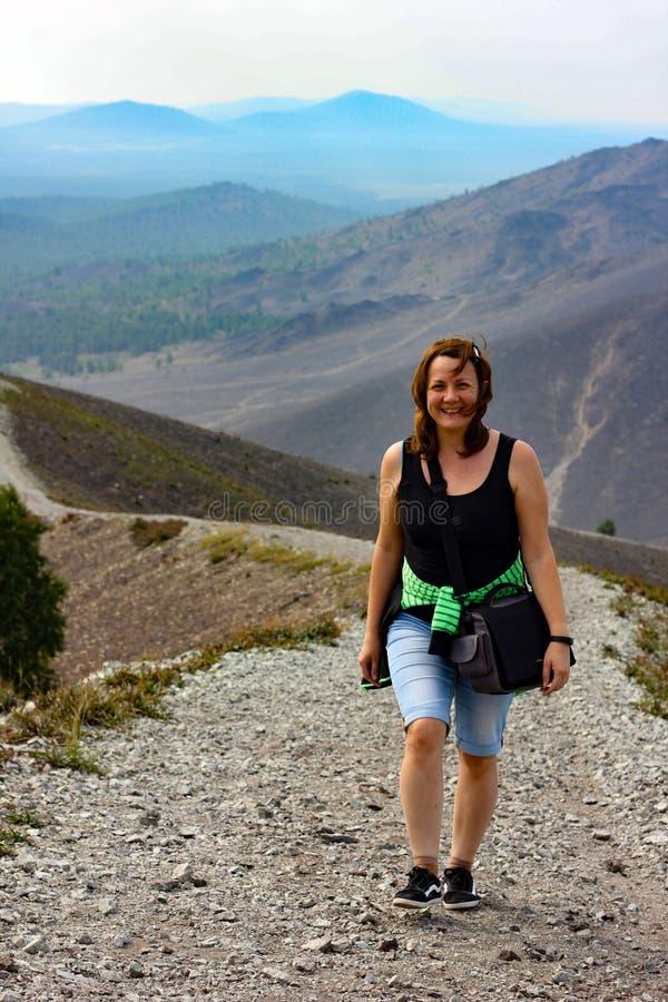 一个愉快的妇女旅客沿山的长的土坎起来上升 免版税库存照片