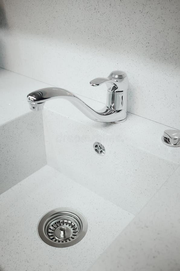 一个新的白色厨房水槽被做人为石头和龙头 现代厨房内部的概念 垂直的摄影 库存图片