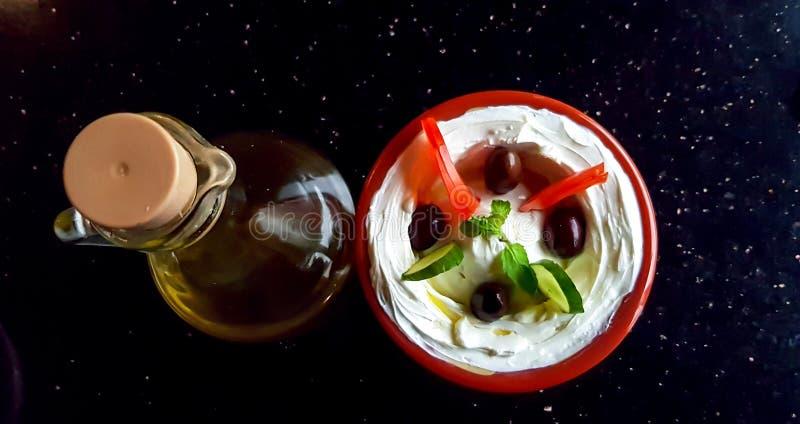 一个碗labneh,阿拉伯酸奶奶油奶酪垂度,与菜和一个瓶橄榄油黑暗的表面上 免版税库存图片