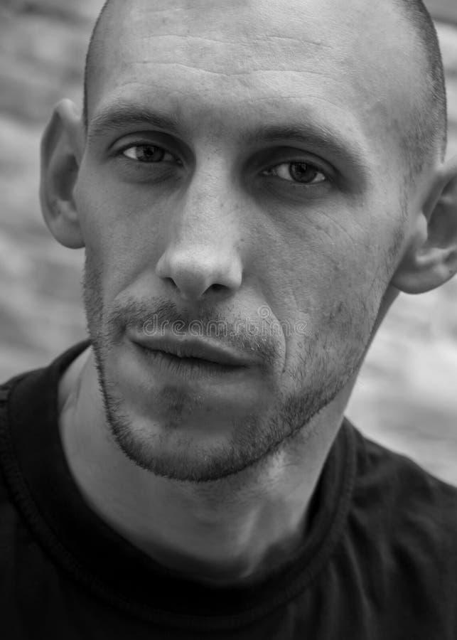 一个秃头人的特写镜头画象有微笑和残酷出现的在黑白 免版税库存照片