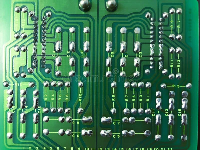 一个绿色计算机电路板的后部的射击在黑背景的 库存图片