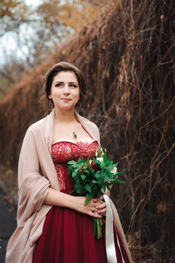 一个美丽的新娘的画象一件红色礼服的有婚姻的花束的在手上 库存图片