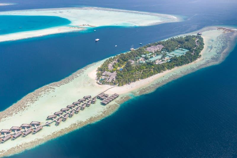 一个热带海岛的鸟瞰图在绿松石水中 在热带海岛度假村马尔代夫的豪华过水别墅 免版税库存图片