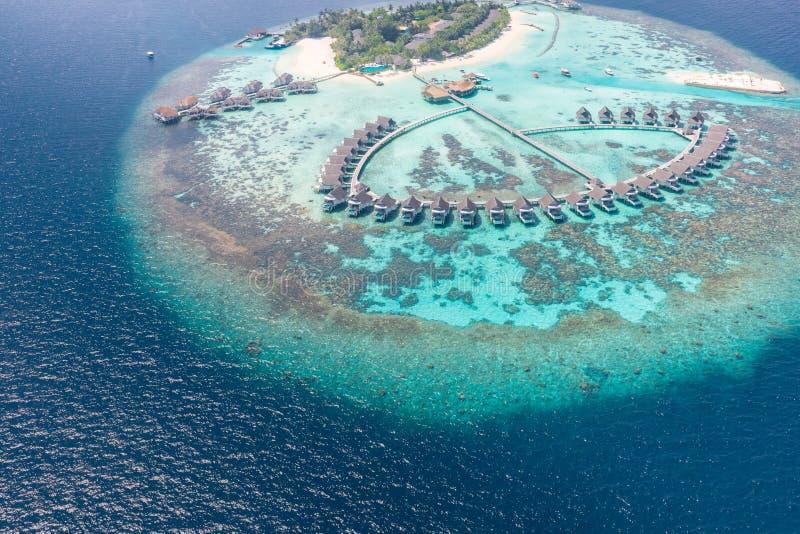 一个热带海岛的鸟瞰图在绿松石水中 在热带海岛度假村马尔代夫的豪华过水别墅 库存图片