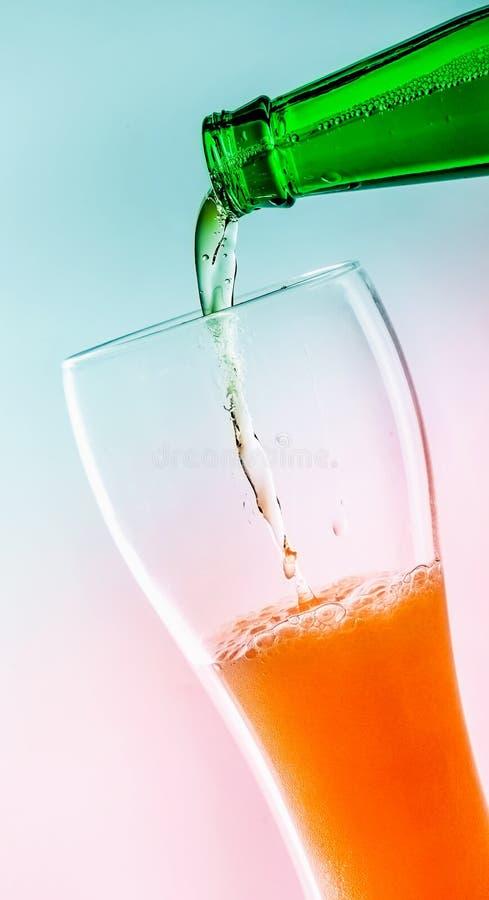 一个瓶绿色玻璃倾吐的啤酒到啤酒杯里 有一个角度 绿松石桃红色背景 特写镜头 免版税库存照片