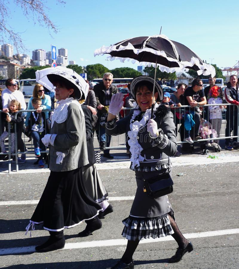 一个狂欢节队伍的夫人与阳伞走在街道上和招呼用他的手 免版税库存照片
