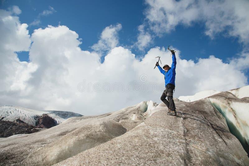 一个盖帽和太阳镜的一个旅客有的被举的胳膊和冰斧符号化在多雪的山的胜利在a 库存图片