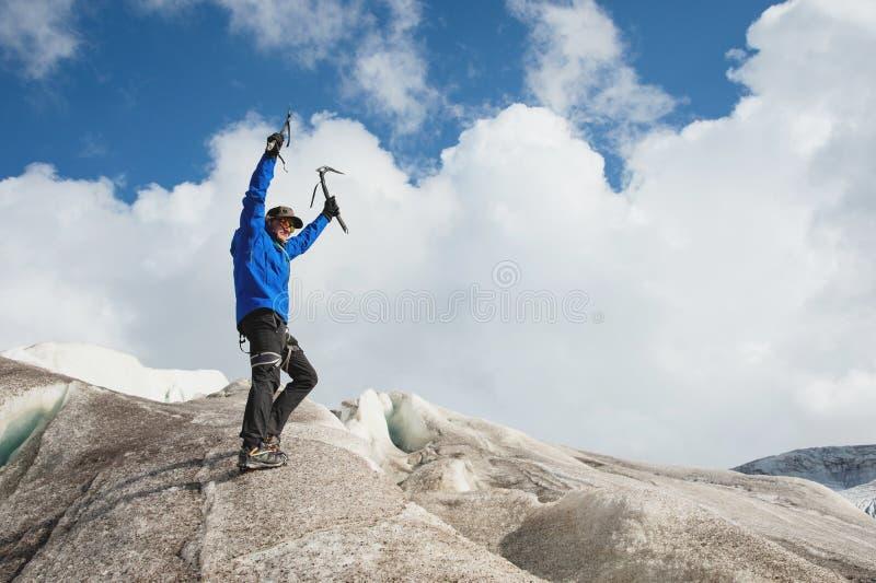 一个盖帽和太阳镜的一个旅客有的被举的胳膊和冰斧符号化在多雪的山的胜利在a 免版税库存图片