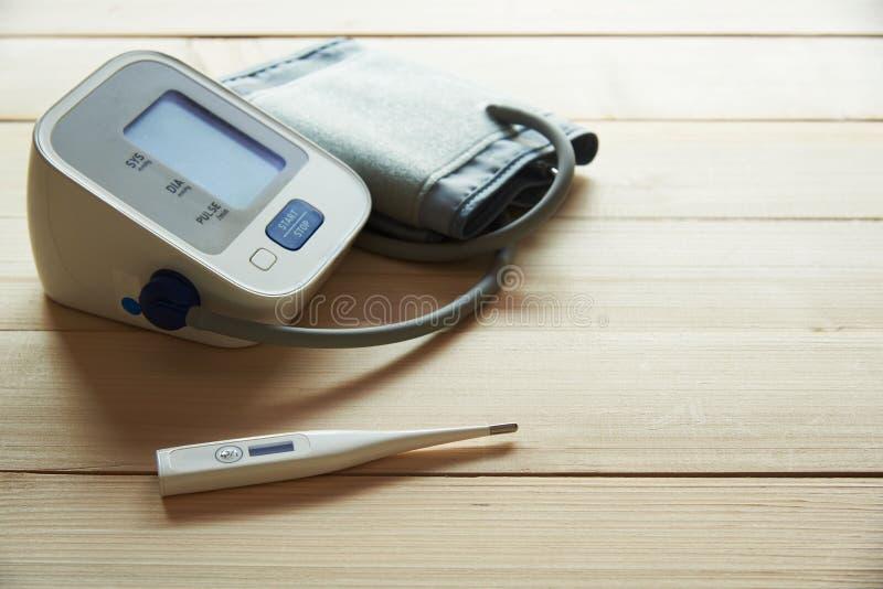 一个白色温度计和血压计在木背景 库存照片