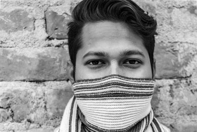 一个男性模型和掩藏他的与围巾的面孔的画象的黑白关闭 免版税库存照片