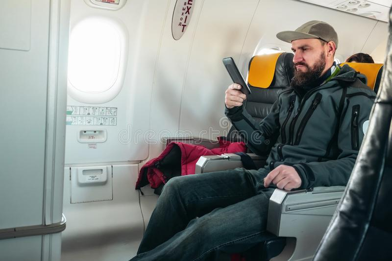 一个男性旅客在飞机时读一eBook,当飞行 免版税库存照片