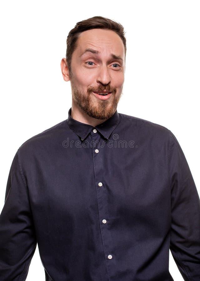 一个英俊,不剃须的人的画象,打扮在一件深蓝衬衣,站立反对白色背景 确信的自 免版税库存图片