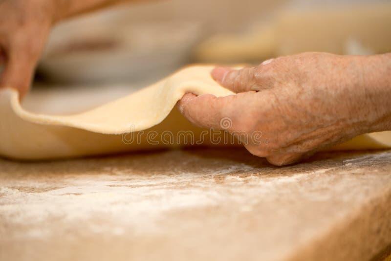 一个老妇人的手铺开面团特写镜头宏指令 库存照片
