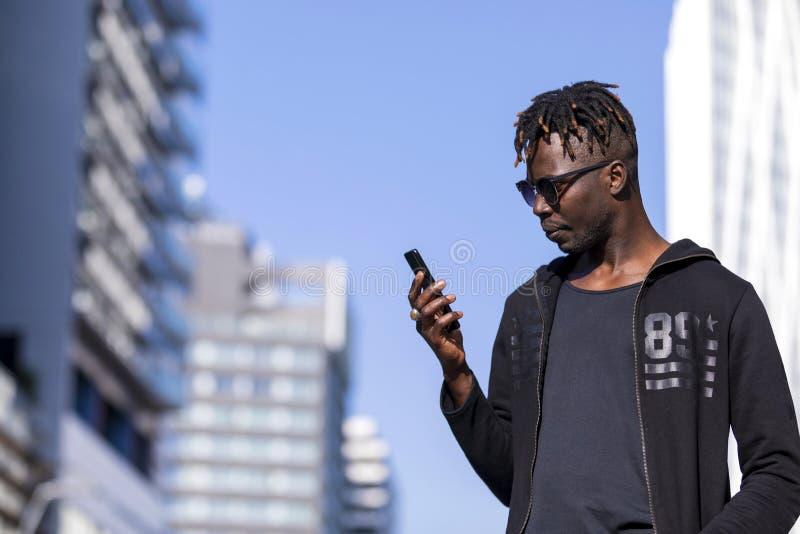 一个非洲黑人年轻人身分的侧视图在街道佩带的便服和太阳镜的,当使用一个手机时 免版税库存图片
