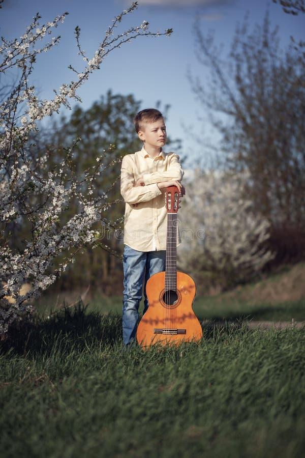 一个青少年身分的画象在春天公园和使用吉他 免版税库存照片