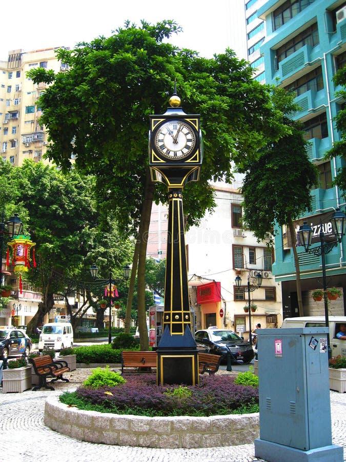 一个高和微小的黑西部大座钟在显示时间的市中心对公众 免版税库存照片
