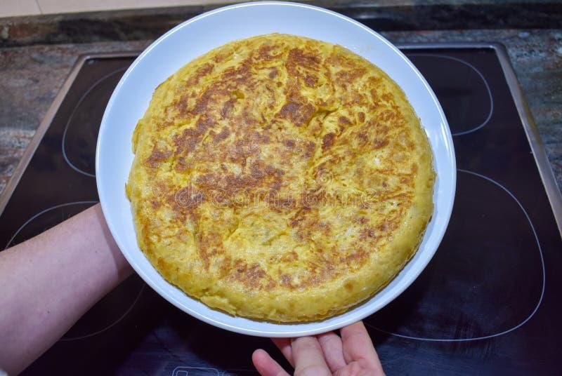 一个鲜美西班牙煎蛋用土豆,在的电磁炉和显示的一个黑煎锅和鸡蛋,烹调的葱 图库摄影