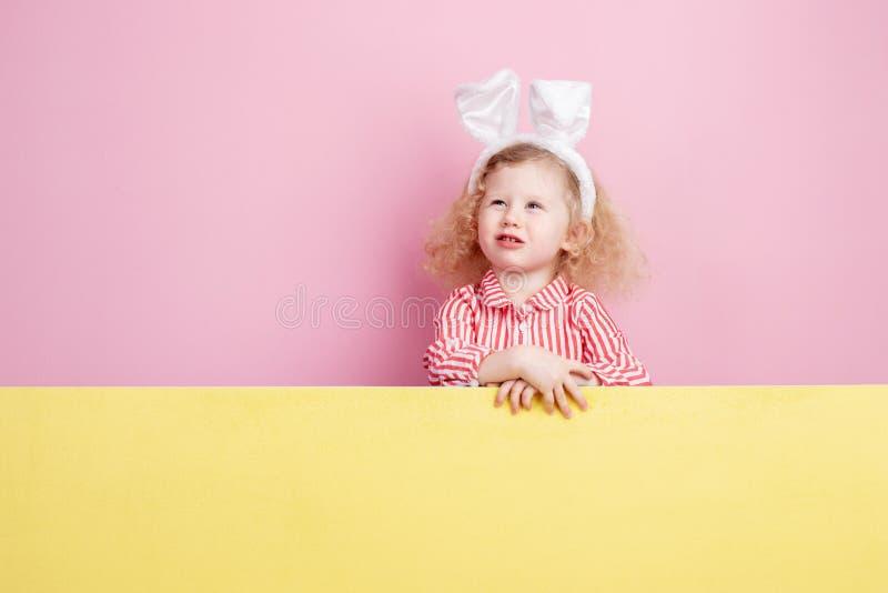 一个镶边红色和白色礼服和兔宝宝耳朵的滑稽的矮小的卷曲女孩在她的在黄色委员会后的顶头立场 库存照片