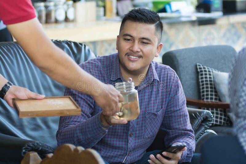 一个attractice亚裔人从咖啡馆侍者接受一块玻璃,当坐在餐馆在白天时 免版税库存照片