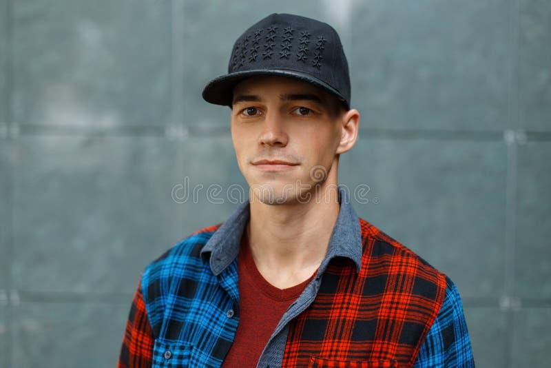 一件五颜六色的葡萄酒方格的衬衣的逗人喜爱的愉快的时髦的年轻人在 T恤杉的一个时兴的黑篮球盖帽 免版税库存照片