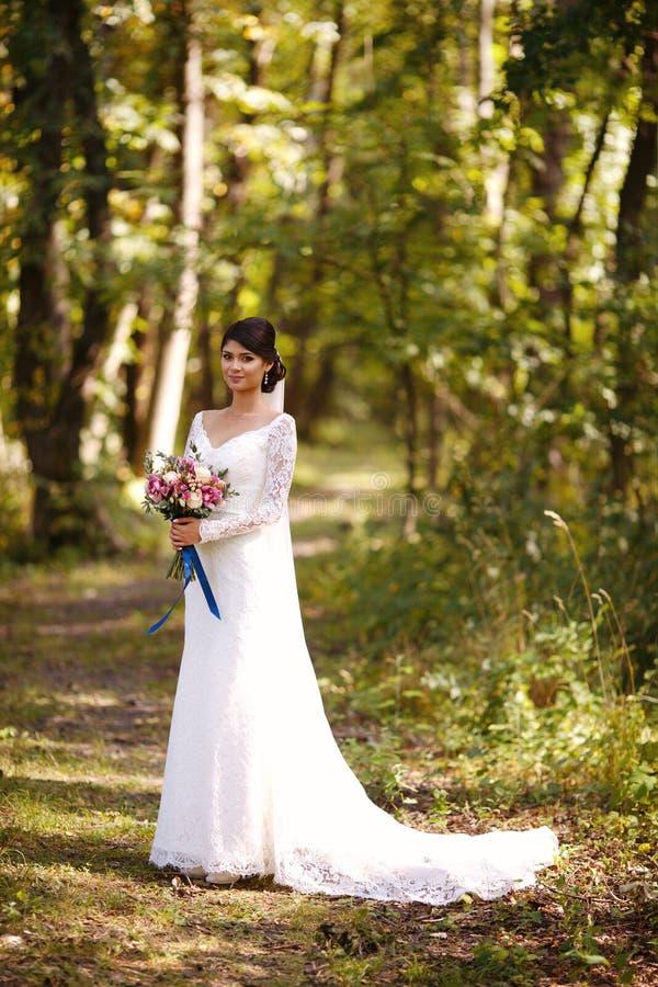 一件婚姻的白色礼服的新娘有一美丽的花束的在她的手上在充分的成长 免版税图库摄影