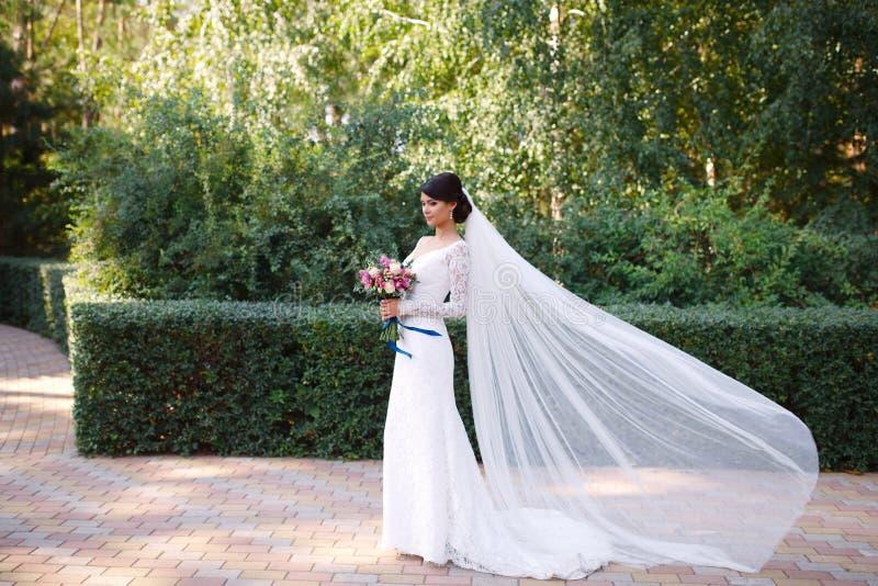 一件婚姻的白色礼服的,在她的头发的长的面纱,花束美丽的新娘在她的手上 免版税图库摄影